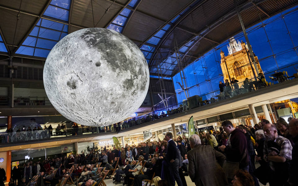 Picture taken inside The Forum, in Norwich. St Peter Mancroft Church can be seen, illuminated, in the background. A giant inflatable moon hangs in the middle of The Forum. People are underneath the moon, looking up at it.