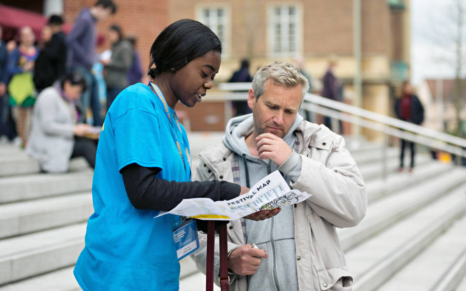 A Festival volunteer helping a member of the public,