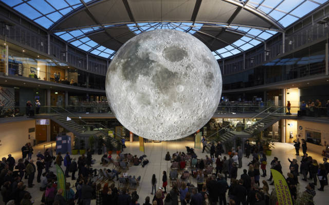 Picture inside the Forum, Norwich. A giant inflatable moon hangs in the middle of the building, it is illuminated. Approx. 100 people stand beneath it, some people sit in deckchairs.