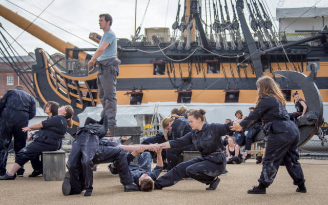 A group of dancers in blue boiler suits perform in front of a ship