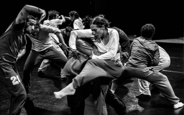 Production photo for Grand Finale, black and white image of lots of people dancing on a big stage.