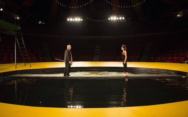 Production photo from NNF16 show The Tempest, two people stand facing each other. Raked seating surrounds them on all sides.