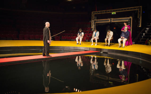 Production photo from NNF16 show The Tempest, five people stand on the edge of the Great Yarmouth Hippodrome Pool, one man stands on a red walkway in the middle of the pool.