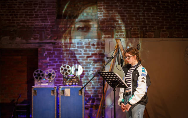 Photo from NNF16 show Wild Like, a girl stands in front of a microphone, a large image of a face is projected on the wall behind her.