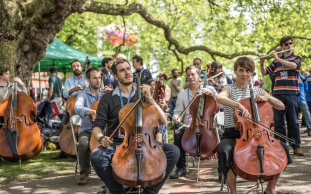 Photo from NNF16 show Beethoven Safari, members of Aurora Orchestra perform outside in Chapelfield Gardens on a sunny day.