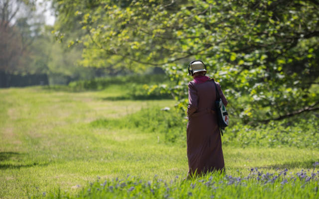 Photo from NNF16 show Walk With Me, a woman dressed in a long purple coat, wearing a pair of headphones and walking through a field.