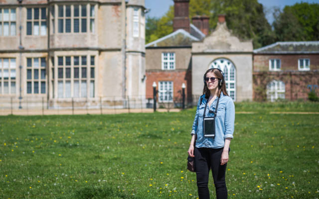 Photo from NNF16 show Walk With Me, a woman stands in front of Felbrigg Hall, she is wearing headphones and an ipad hangs around her neck.