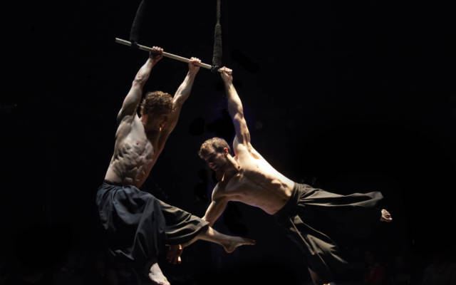 Photo from NNF15 show What Will Have Been, two men hang from a trapeze.