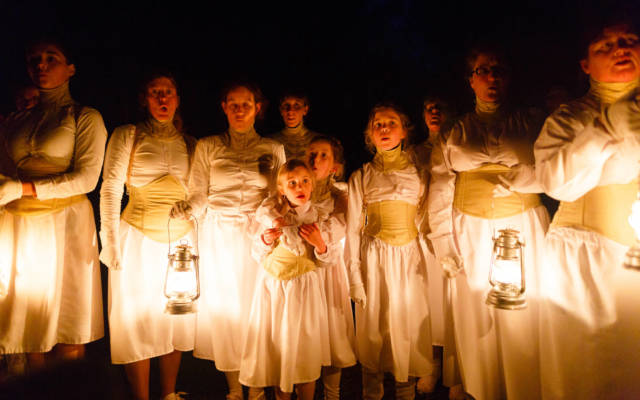 Photo from NNF15 show Wolf's Child, a group of women and young girls stand in a line. They are wearing white dresses and corsets, four of them are holding lanterns, it is night time.