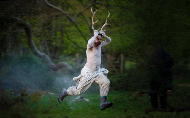 Photo from NNF15 show Wolf's Child, a man painted in white, holds two antlers to his head and runs through a woodland area.
