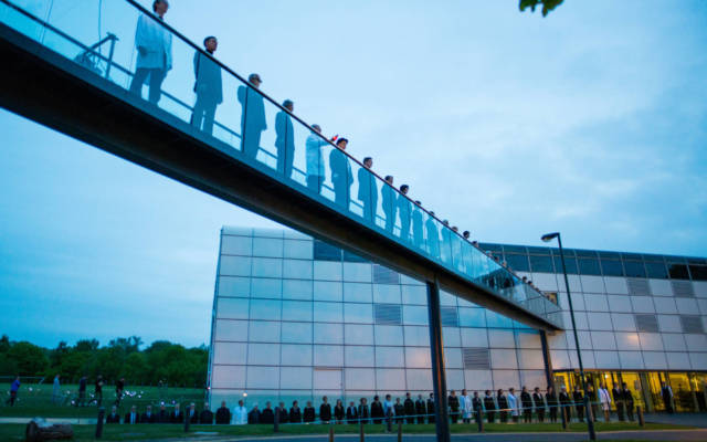 Photo from NNF15 show The Observatory, a long line of people stand on a raised walkway leading to the Sainsbury Centre for Visual Arts.