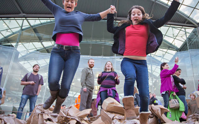 Photo from NNF14 show The Peoples Tower, two women jump in the air on top of a big pile of cardboard boxes.