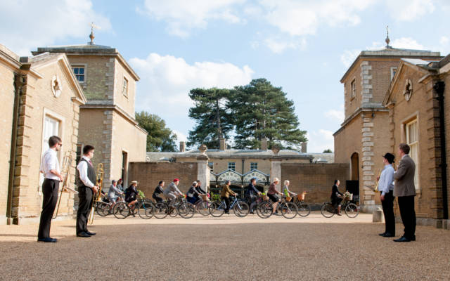 Photo from NNF14 show Souvenir, a group of approx 10 people ride bikes through the courtyard at Holkham Hall.