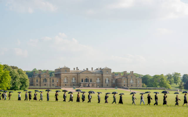 Photo from NNF14 show Souvenir, a long procession of people walk through a field, each holding a black umbrella. Holkham Hall is visible in the background.
