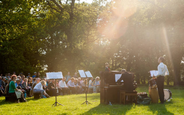 Photo from NNF14 show Souvenir, set outside in a wooded area on a sunny day. A large crowd watch a man playing a piano.
