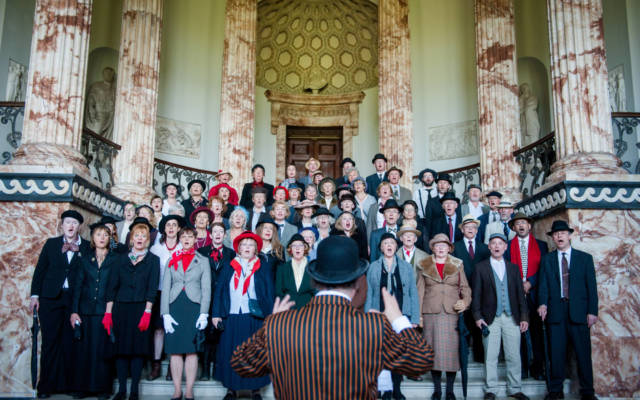 Photo from NNF14 show Souvenir, a group of approx forty choir members dressed in 1920s attire stand on a grand staircase.