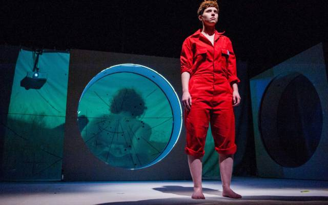From NNF14 show Pioneer, a woman dressed in red boilersuit stands on stage with blue backdrop.