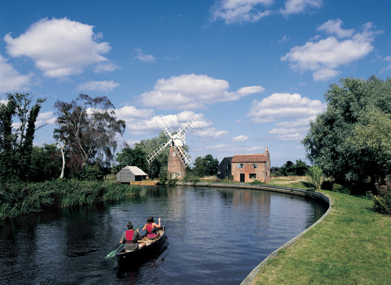 Two people canoe down a bending river, it is a sunny day. A windmill can be seen in the distance.