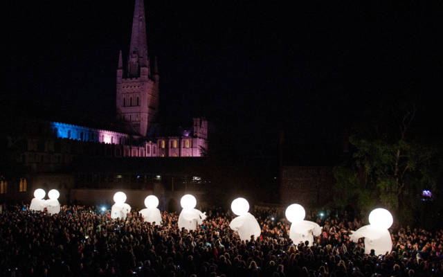 Photo from NNF13 show Reve dHerbert. It is night time. In the background there is Norwich Cathedral, which is illuminated in a purple/blue light. In the foreground there are hundreds of people, all gazing at eight large, white, glowing, inflatable figures.