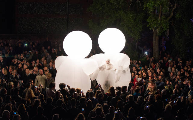 Photo from NNF13 show The Kindness of Strangers, two huge white, inflatable figures stand facing each other, surrounded by a big crowd.