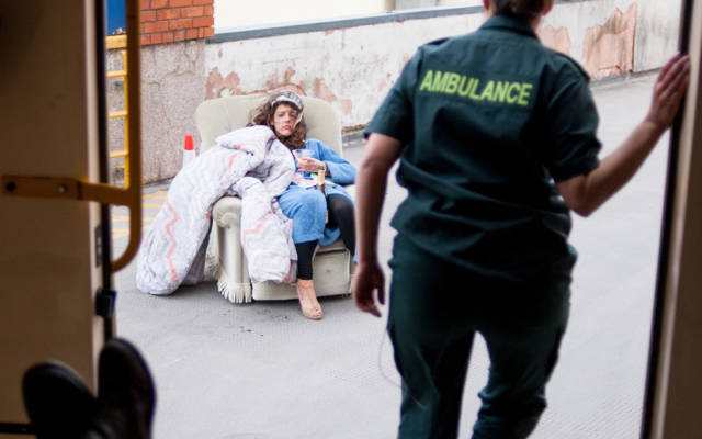 Photo from NNF13 show The Kindness of Strangers, taken from inside an ambulance with the back doors open, a paramedic steps out of the ambulance. There is a woman sitting on a chair on the pavement outside.