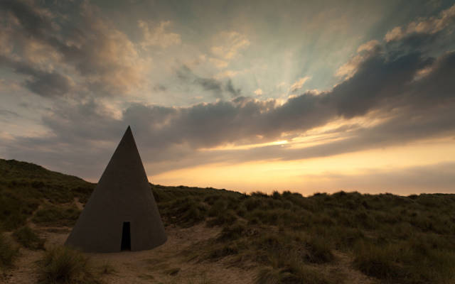Photo from NNF12 show Walking, a large cone with a small cut out door sits on a sand dune.