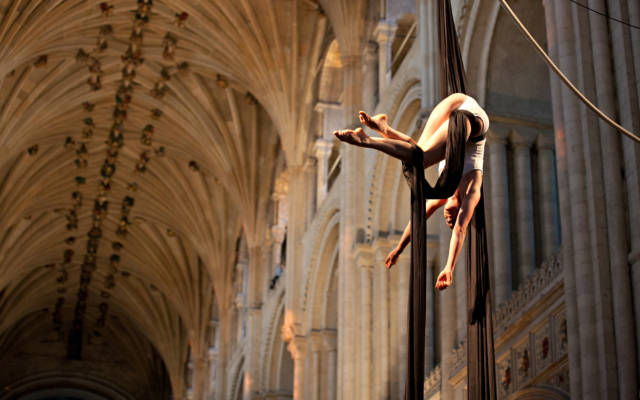 Photo from NNF12 show How Like An Angel, a woman hangs from two pieces of silk in Norwich Cathedral.