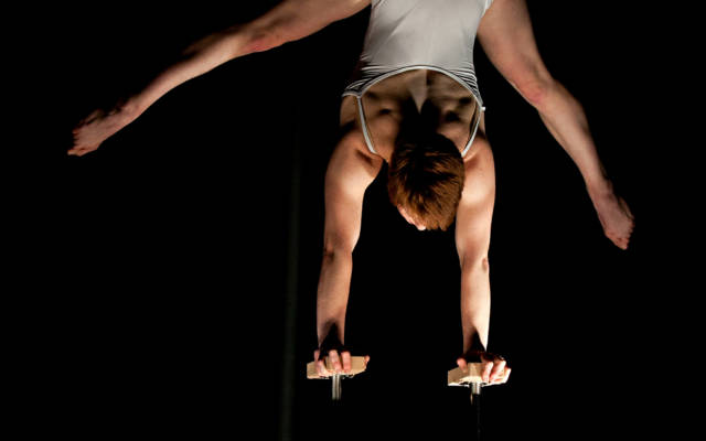 Photo from NNF12 show How Like An Angel, a circus performer stands on her hands on two small plinths.