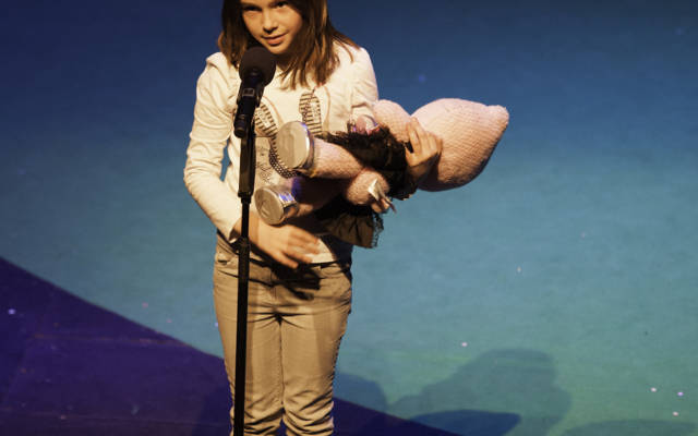 Photo from NNF12 show 100% Norfolk, a little girl stands on stage holding a pink toy. She is talking into a microphone.