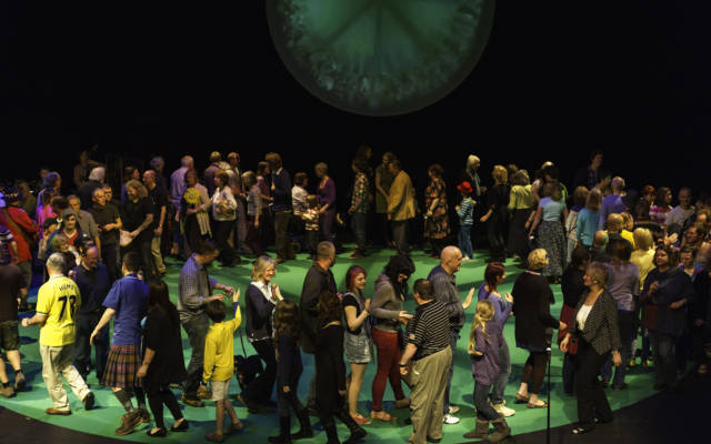 Photo from NNF12 show 100% Norfolk, a group of 100 people on stage, walking around in a big circle.