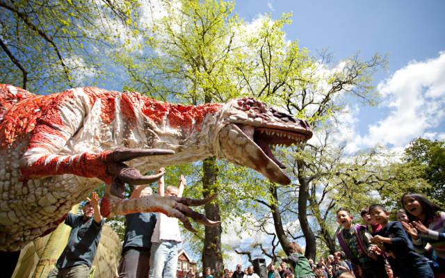 Photo from NNF12 show Dinosaur Petting Zoo, a huge T-rex puppet faces an audience of children who are all standing up and clapping.