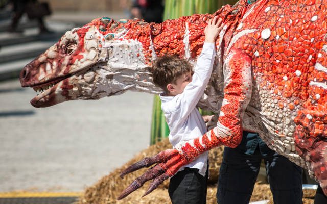 Photo from NNF12 show Dinosaur Petting Zoo, a little boy gives a huge T-Rex puppet a hug.