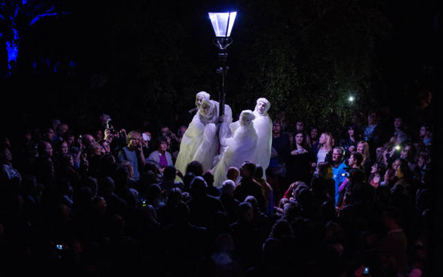 Photo from NNF13 show Reve dHerbert, four men standing on tall stilts dressed all in white, hold onto an old style street lamp. They are surrounded by a large crowd.