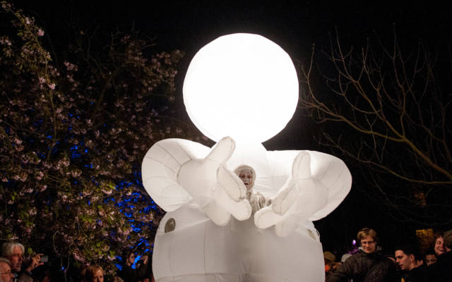Photo from NNF13 show Reve dHerbert, a man dressed all in white, standing within a huge white glowing suit.