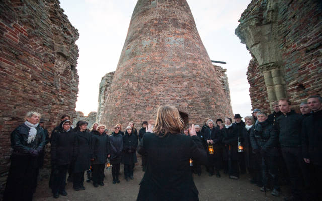 Photo from NNF13 show Ideas of Flight, a choir of approx. 20 members, all dressed in black, stand in the middle of a derelict building.