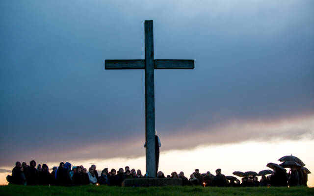 Photo from NNF13 show Ideas of Flight, a large audience watch a man who is standing in front of a huge wooden crucifix.