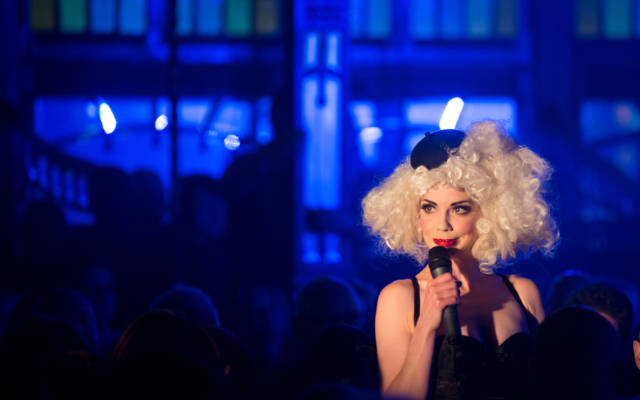 Photo from NNF13 show Les Enfants Perdus, a woman wearing a big blonde wig and a tiny black beret holds a microphone to her mouth.
