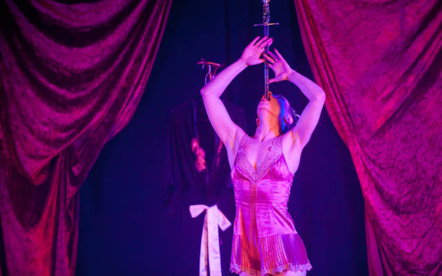 Photo from NNF13 show Les Enfant Perdus, a woman on stage, swallowing a sword.