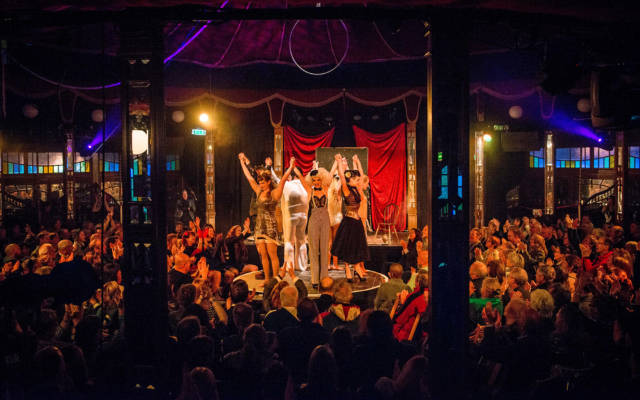 Photo from NNF13 show Les Enfants Perdus, a group of performers stand on a circular stage in the spiegeltent, a busy crowd surrounds them, clapping.