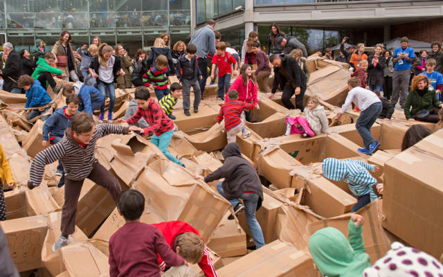 Photo from NNF14 show The Peoples Tower, tens of people stomp over the remains of a large cardboard structure.