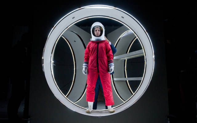 Photo from NNF14 show Pioneer, a woman dressed in a red spacesuit and white space helmet.