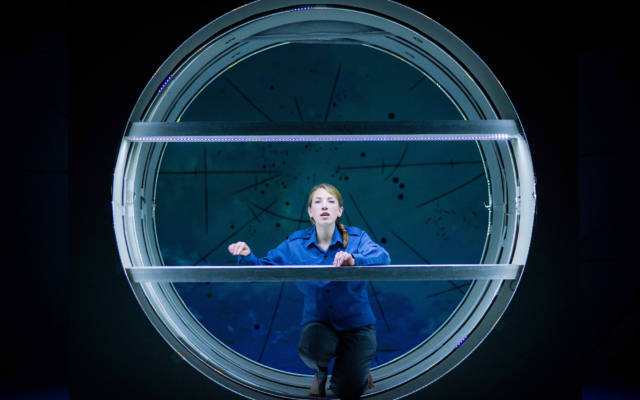 Photo from NNF14 show Pioneer, a woman dressed in blue with her hair in a plait kneels in a big circular space, staring at the camera.