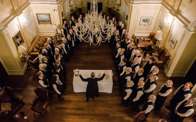 Photo from NNF17 show The Arms of Sleep, taken from above. The Voice Project Choir stand in a semi-circle with a table in between them.