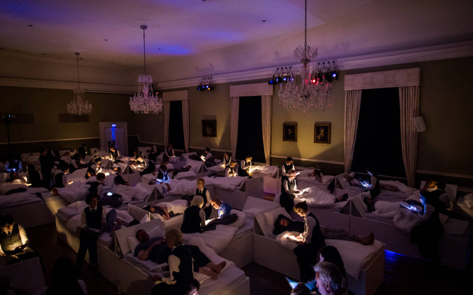 Photo from NNF17 show The Arms of Sleep, approx. 40 beds are arranged in a large room. Audience members lie one per bed, and members of the choir sit on the end of each bed.