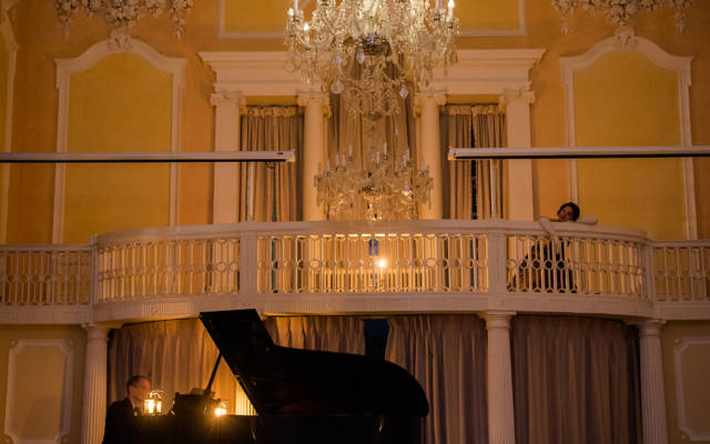 Photo from NNF17 show The Arms of Sleep, taken inside a grand room with yellow walls and a chandelier hanging from the ceiling. A man is playing piano on stage.