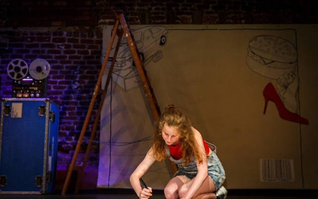 Photo from NNF16 show Wild Life, a woman sits on stage, drawing on a large piece of paper.