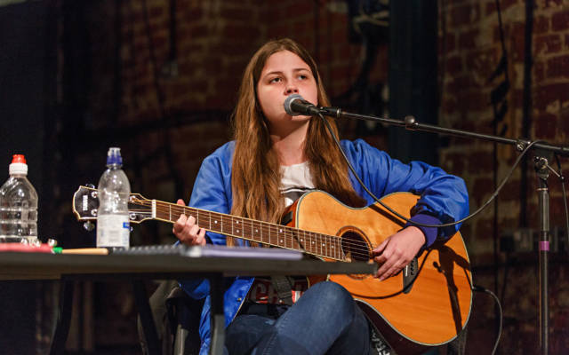 Photo from NNF16 show Wild Life, a woman sits on stage playing a guitar and singing.