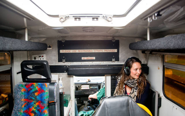 Photo from NNF13 show The Kindness of Strangers, a woman wearing a pair of headphones sitting in the back of an ambuland & gazing out of the window.