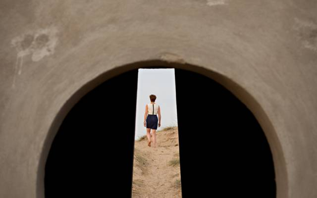 An image taken through a hole, you can see a woman walking away from the camera.