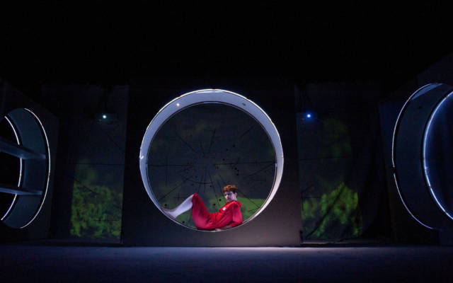 A woman in a red boiler suit sits in a large block on stage. The background is a projection of a woodland area.